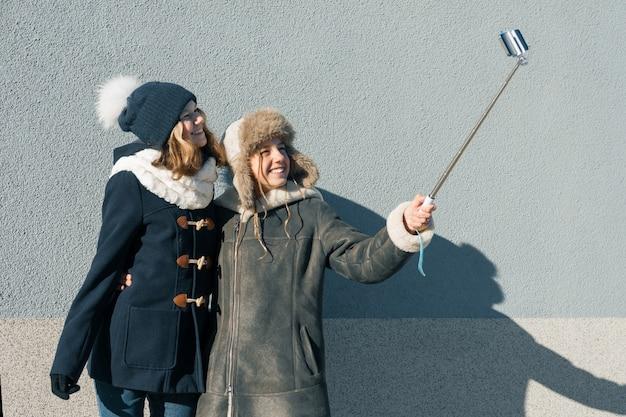 Felizes namoradas sorridentes em roupas de inverno, tendo selfie