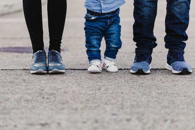 Felizes pais elegantes de mãos dadas com o menino e andando pela rua, concurso momento familiar.