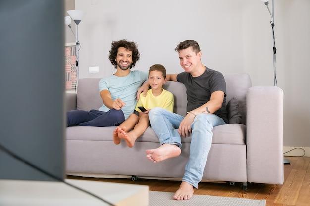 Felizes pais gays e filho assistindo programa engraçado de tv em casa, sentado no sofá da sala, sorrindo e rindo. conceito de entretenimento familiar e doméstico