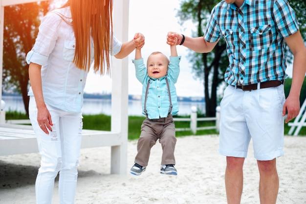 Felizes pais jovens com filho jogando ao ar livre no parque