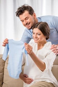 Felizes pais jovens estão segurando as roupas do seu futuro bebê.