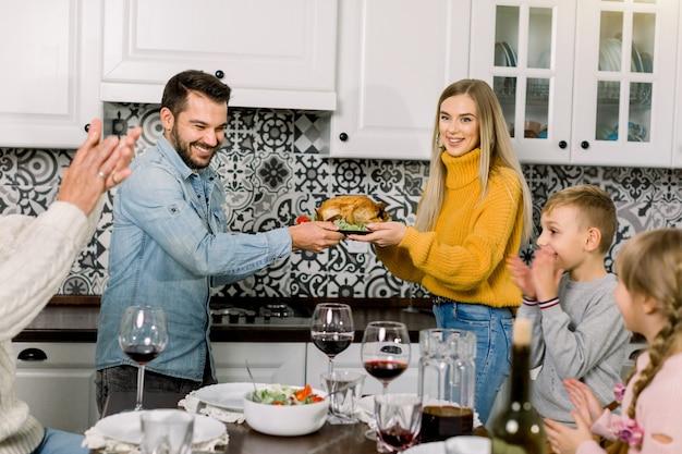 Felizes pais jovens, mulher e homem, oferecendo frango assado para a família, filhos e avô, jantando em casa
