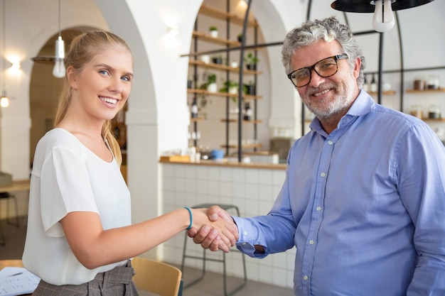 Felizes parceiros de negócios de diferentes idades se encontrando e apertando as mãos