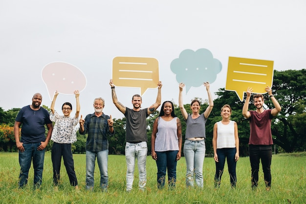 Felizes pessoas diversas segurando balões coloridos de fala