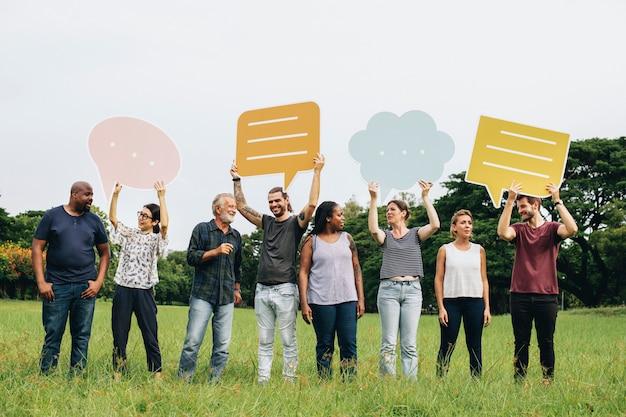 Felizes pessoas diversas segurando balões de fala colorido
