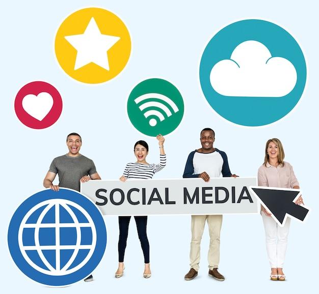Felizes pessoas diversas segurando ícones de mídia social