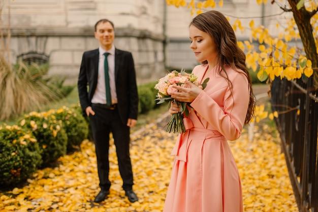 Felizes recém-casados estão andando no parque outono perto da catedral vintage e segurando o buquê de casamento.
