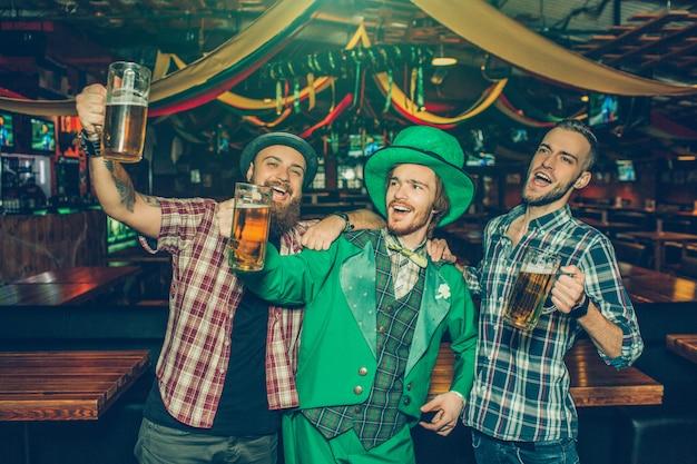 Felizes três jovens cantando e acenando com canecas de cerveja no pub. eles olham para a esquerda. cara no meio usa roupa de são patrício.