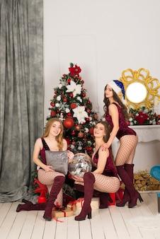 Felizes três lindas garotas com uma cor de cabelo diferente, donzela de neve em fantasias de natal, sacola de presente.