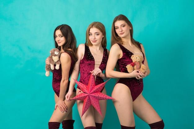 Felizes três lindas garotas com uma cor de cabelo diferente, donzela de neve em uma fantasia de natal com saco de presente.