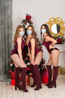 Felizes três lindas garotas em máscara protetora com cor de cabelo diferente, donzela de neve em uma fantasia de natal com saco de presente.