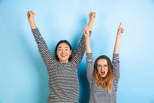 Felizes vencedores, apontando. jovens mulheres emocionais isoladas na parede azul gradiente. conceito de emoções humanas, expressão facial, amizade, anúncio. lindas modelos caucasianos com roupas casuais.