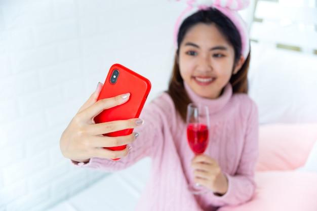 Felizmente adolescente desfrutando selfie com vinho tinto na mão