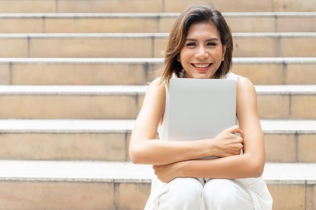 Felizmente jovem bonito abraçando laptop na escada