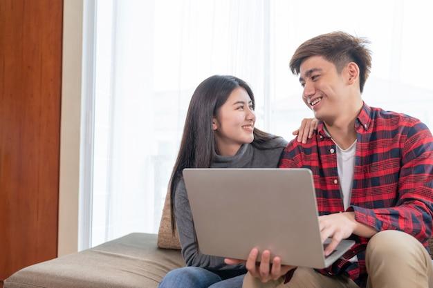 Felizmente jovem mulher bonita e homem bonito usando computador portátil no sofá no quarto em casa