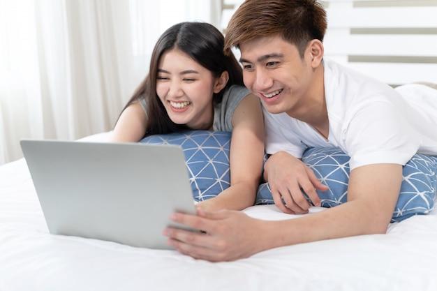 Felizmente jovem mulher bonita e homem bonito, usando o computador portátil na cama no quarto em casa