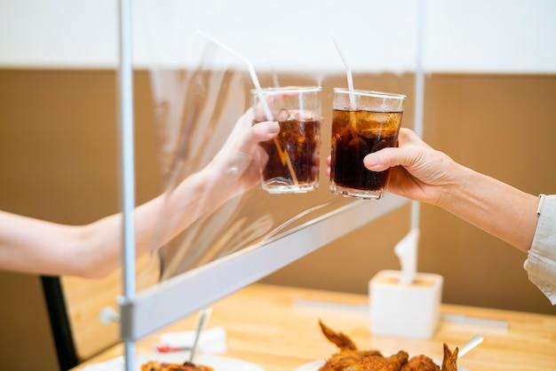 Fêmea a tilintar um copo de água com a mãe, sentada com uma mesa divisória de protecção de plástico num restaurante