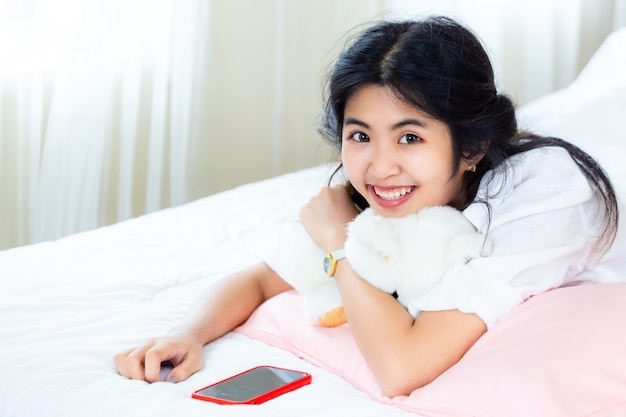 Fêmea adolescente bonita alegre com smartphone na cama