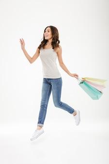 Fêmea adulta em êxtase de corpo inteiro, levitando ou pulando com muitas sacolas coloridas na mão, isoladas sobre o branco