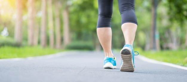 Fêmea adulta jovem em sapatos de esporte correndo no parque ao ar livre