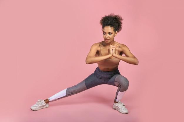 Fêmea africana muito esportiva, fazendo exercícios, posando no bagkground rosa.