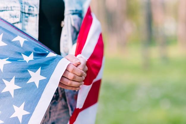 Fêmea anônima envolvendo na bandeira americana enquanto celebra o dia da independência
