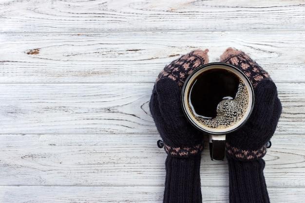 Fêmea as mãos em luvas segurando uma xícara de café sobre fundo de madeira
