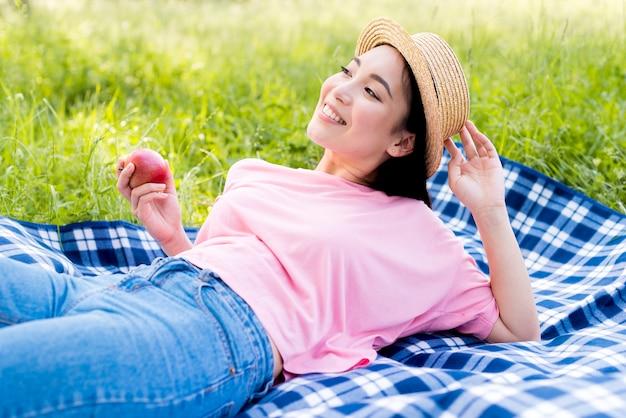 Fêmea asiática, com, maçã, mentindo, ligado, pano