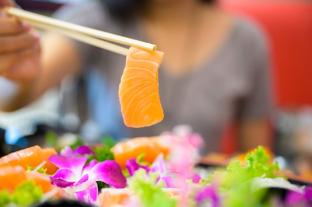 Fêmea asiática que come o sashimi salmon
