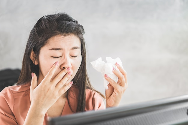 Fêmea asiática tendo gripe espirros no local de trabalho