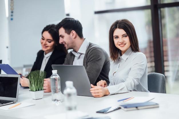 Fêmea bem sucedida usando laptop em seu trabalho no escritório.
