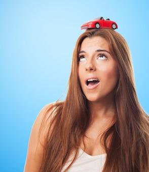 Fêmea bonita com um carro pequeno na cabeça
