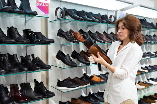 Fêmea branca surpresa olha para o lado único de sapatos masculinos.