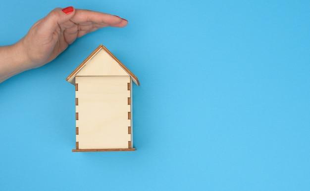 Fêmea cede a casa modelo em miniatura de madeira sobre fundo azul. conceito de seguro imobiliário, proteção ambiental, espaço de cópia