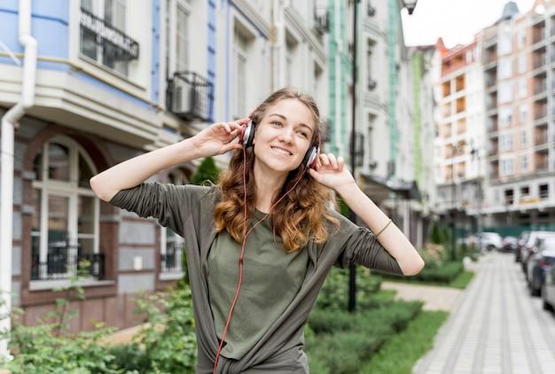 Fêmea com fones de ouvido, curtindo música