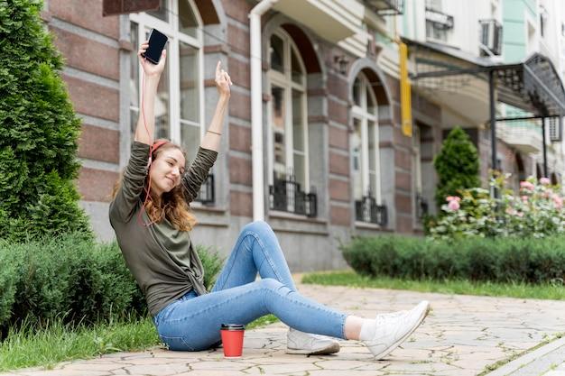 Fêmea com fones de ouvido, ouvindo música