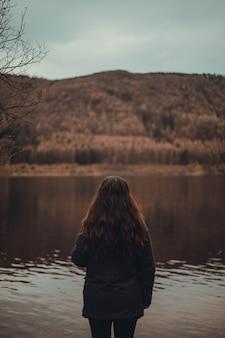 Fêmea com longos cabelos vermelhos em pé perto de um lago em uma floresta