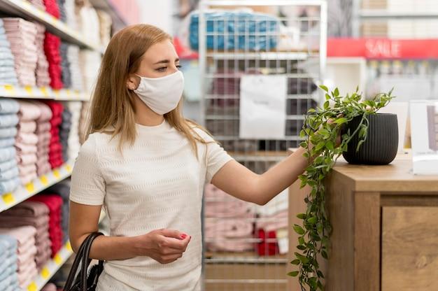 Fêmea com máscara em compras