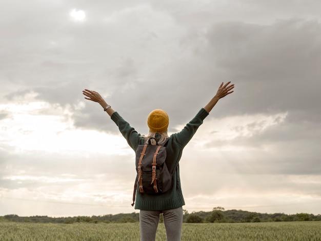 Fêmea com mochila com as mãos levantadas