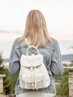 Fêmea com mochila na costa do mar