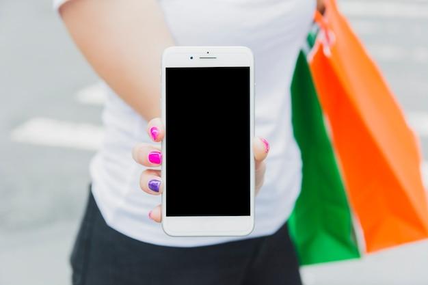 Fêmea com telefone e sacolas de compras