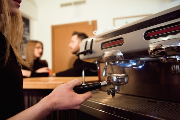 Fêmea, começando o dia em um novo emprego como barista. trabalhando em um café.