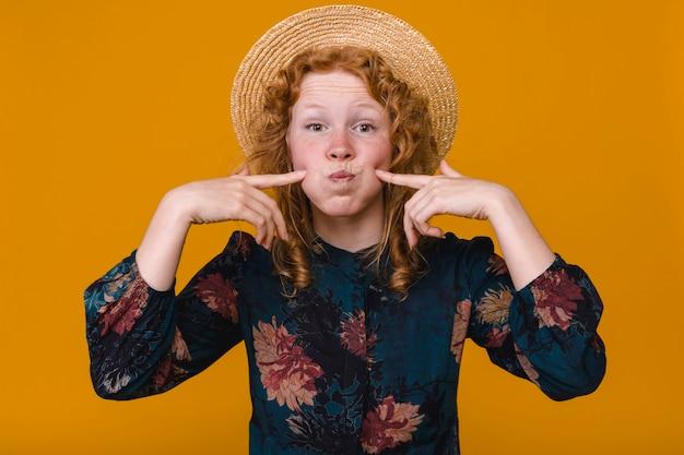 Fêmea curly amusing com cabelo do gengibre que engana ao redor no estúdio com fundo colorido