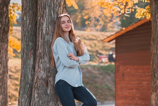 Fêmea de ângulo baixo no par em pé ao lado da árvore