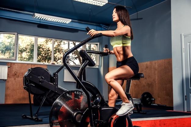 Fêmea de aptidão usando bicicleta de ar para treino cardio no ginásio crossfit.