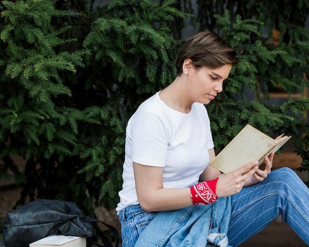 Fêmea de cabelos curtos que senta-se com o livro no parque