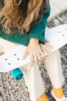 Fêmea de close-up ao ar livre com skate