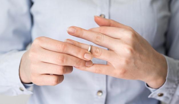 Fêmea de close-up, retirando o anel de casamento