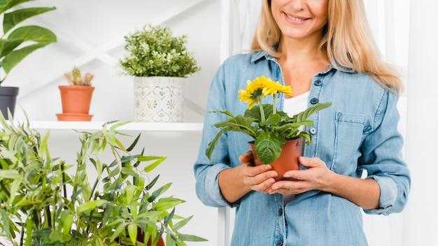 Fêmea de close-up, segurando o vaso de flores