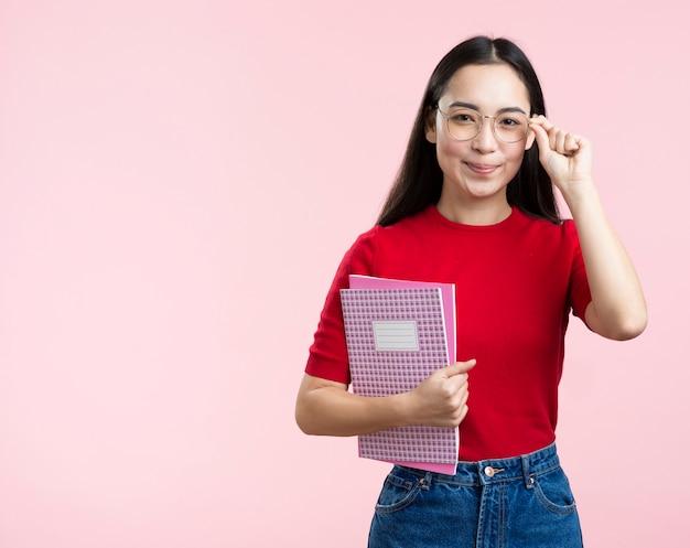 Fêmea de cópia-espaço com óculos e livro